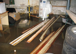 A severely flooding basement in Newark, with lumber and personal items floating in a foot of water
